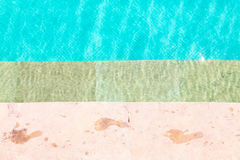 Wet foot prints on side of swimming pool Stock Photos