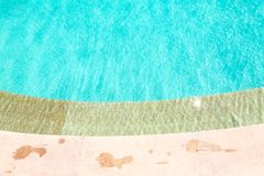 Wet foot prints on side of turquoise swimming pool Royalty Free Stock Photography