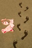 Wet footsteps on tiles. Image shows some wet footsteps next to bikini. Image was taken near a swimming pool in Belgium, Europe royalty free stock photo