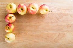Wet fuji apple on wood chop block and on wood table Stock Photography