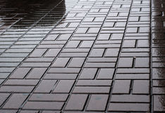 Wet geometric pattern of urban pavement Royalty Free Stock Photo