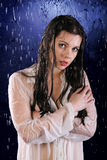 The wet girl. The blotted girl in white tunic in water splashes on a dark blue background royalty free stock photos