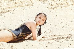 A wet girl with dark hair in a black bathing suit lies on the sand after swimming in the river stock photography