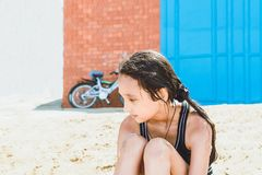 A wet girl with dark hair in a black bathing suit sits on the sand after swimming in the river stock photos