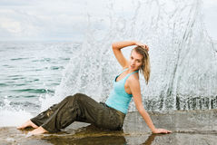 Wet girl sitting near the ocean. Wall of water behind her Stock Photography