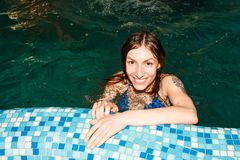 Wet girl in the swimming-pool. In the evening Royalty Free Stock Image