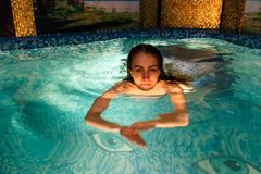 Wet girl in the swimming-pool. In the evening Stock Images