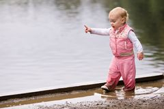 Wet girl toddler in puddle Royalty Free Stock Photo