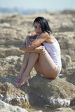 Wet girl in white tank top sitting on rocky beach Royalty Free Stock Photos