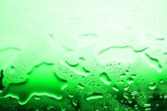 Wet glass surface in drops of water, green gradient, illustration of cood or cold bottle of beer, texture of spilled water stock image
