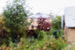 Wet glass of window backgrounds. Wet glass of window of country house, view countrye from indoors royalty free stock photo