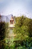 Wet glass of window backgrounds. Wet glass of window of country house, view countrye from indoors royalty free stock images