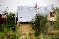 Wet glass of window backgrounds. Wet glass of window of country house, view countryside from indoors stock photo