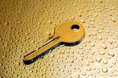 Wet gold key. Gold key on a golden droplets background Royalty Free Stock Photo