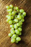 Wet grapes on a wooden table Stock Images