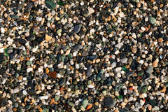 Wet Gravel. Closeup on wet gravel along the seashore. Small peaces of smooth colored glass are visible too stock photos