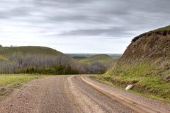 Wet gravel road winding around green hills. Stock Image