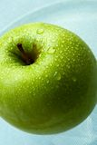 Wet green apple. In brilliant drops of water royalty free stock photos