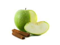 Wet green apple with slice and cinnamon. Sliced wet green apple with slice and cinnamon pods (white background). Fresh diet fruit. Healthy fruit with vitamins Royalty Free Stock Photo