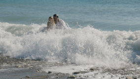 Wet groom and bride have fun in the water. A man and a woman go to the shore and fall. The newlyweds get up and the wave covers them from behind. Young people stock footage