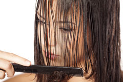 Wet hair combing. Beautiful young woman combing her wet hair Royalty Free Stock Image