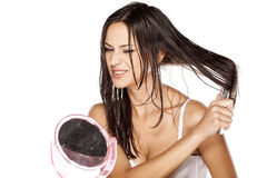 Wet hair combing. Unhappy beautiful young woman combing her wet hair Stock Image