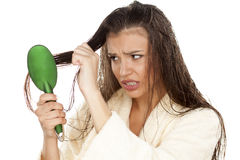 Wet hair combing. Young beautiful and nervous woman in a bathrobe combing her wet hair Stock Photo
