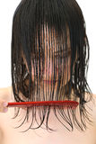 Wet hair in the face. Young girl combing her wet hair Royalty Free Stock Photos