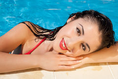 Wet hair woman. Pretty woman with wet hair at the edge of the swimming pool on a hot day Stock Image