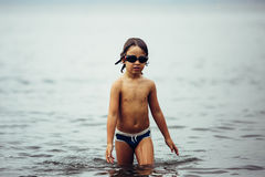 Wet-haired kid in goggles walking in sea Stock Images