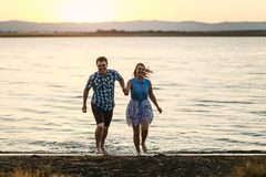 Wet lovers run out of the water at sunset. Wet happy lovers run out of the water at sunset stock photo