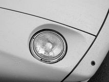 Wet Headlight. A recessed headlight on a Porsche 928 just after a rain shower stock images