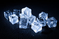 Wet ice cubes on black background Stock Photos