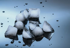Wet ice cubes on black glossy  background Stock Photos