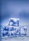 Wet ice cubes on blue background Stock Photos