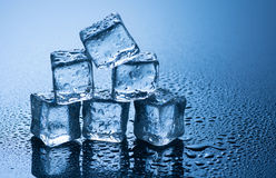 Wet ice cubes on blue background Royalty Free Stock Photography