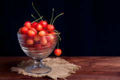 Wet juicy cherries in a bowl on wooden table. Cherries in a glass bowl on wooden table Stock Images