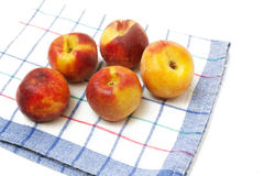 Wet juicy peaches lying on kitchen towel Royalty Free Stock Photo