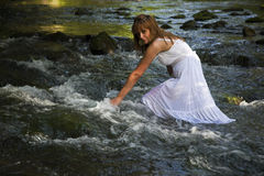 Wet Lady Walking Cross River Stock Photo