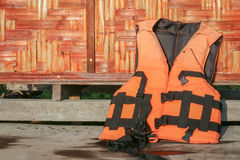 Wet life vest. Put on the wood floor and lean on orange weaving bamboo wall for aerating Stock Images