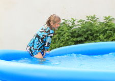 Wet little girl getting into pool. Wet little girl in blue - black - white t-shirt getting into a blue pool Stock Images