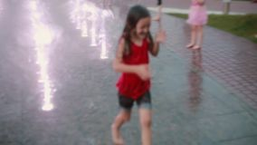 Wet little girl running through the water jets at the fountain and laughing. Child having fun in hot summer day.