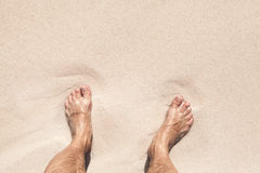 Wet male feet stand on white sand Royalty Free Stock Image