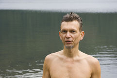 Wet man after a swim in a lake. With a grey chin-beard Royalty Free Stock Image
