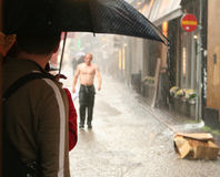 Wet man walking. Man with umbrella waiting when stop raing and another man, walking in the rain 1 : Should I wait or should I go royalty free stock photo