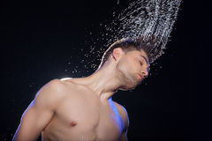 Wet men. Portrait of young man with wet hair standing isolated on black royalty free stock photography