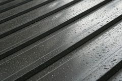 Wet metal roof detail. Dark wet metal roof detail with raindrops stock photo