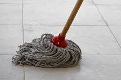 Wet mop on dirty tile stock images
