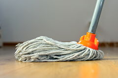 Wet mop on wooden floor. Cleaning wooden floor with orange wet mop Stock Image