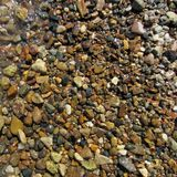 Wet multi-colored gravel on the river bank. Royalty Free Stock Image